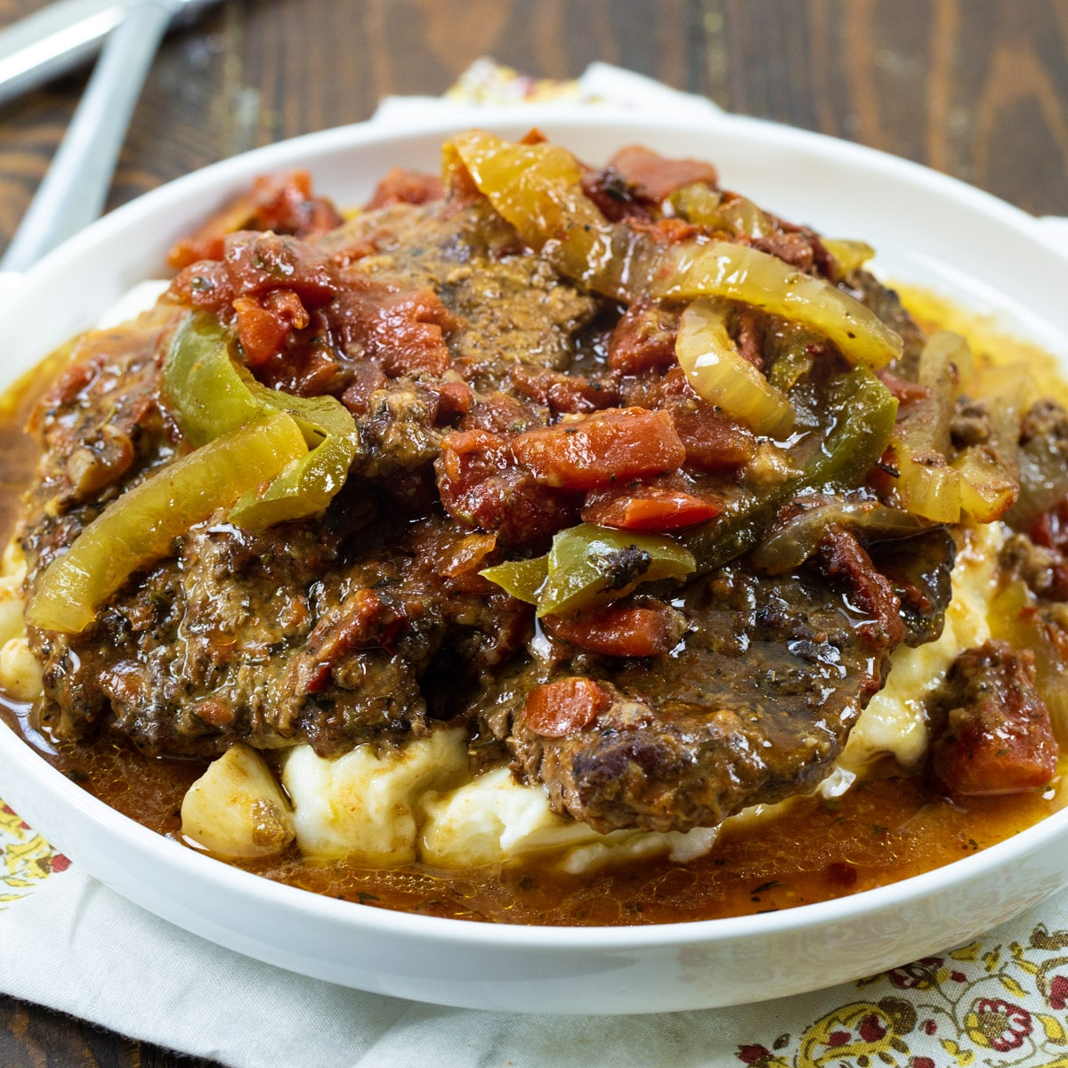 Slow Cooker Swiss Steak over mashed potatoes on a plate.