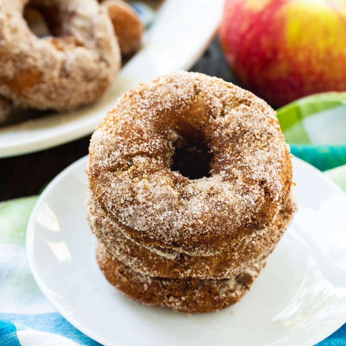 Apple Cider Doughnuts stacked on a plate.