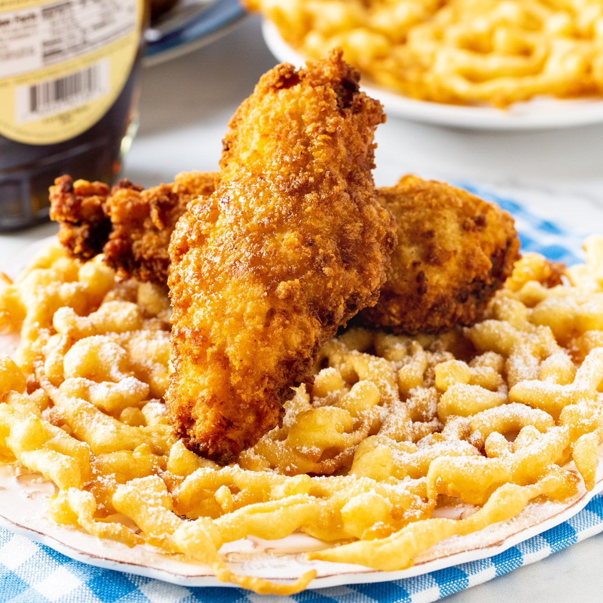 Two fried chicken tenders on top of funnel cake.
