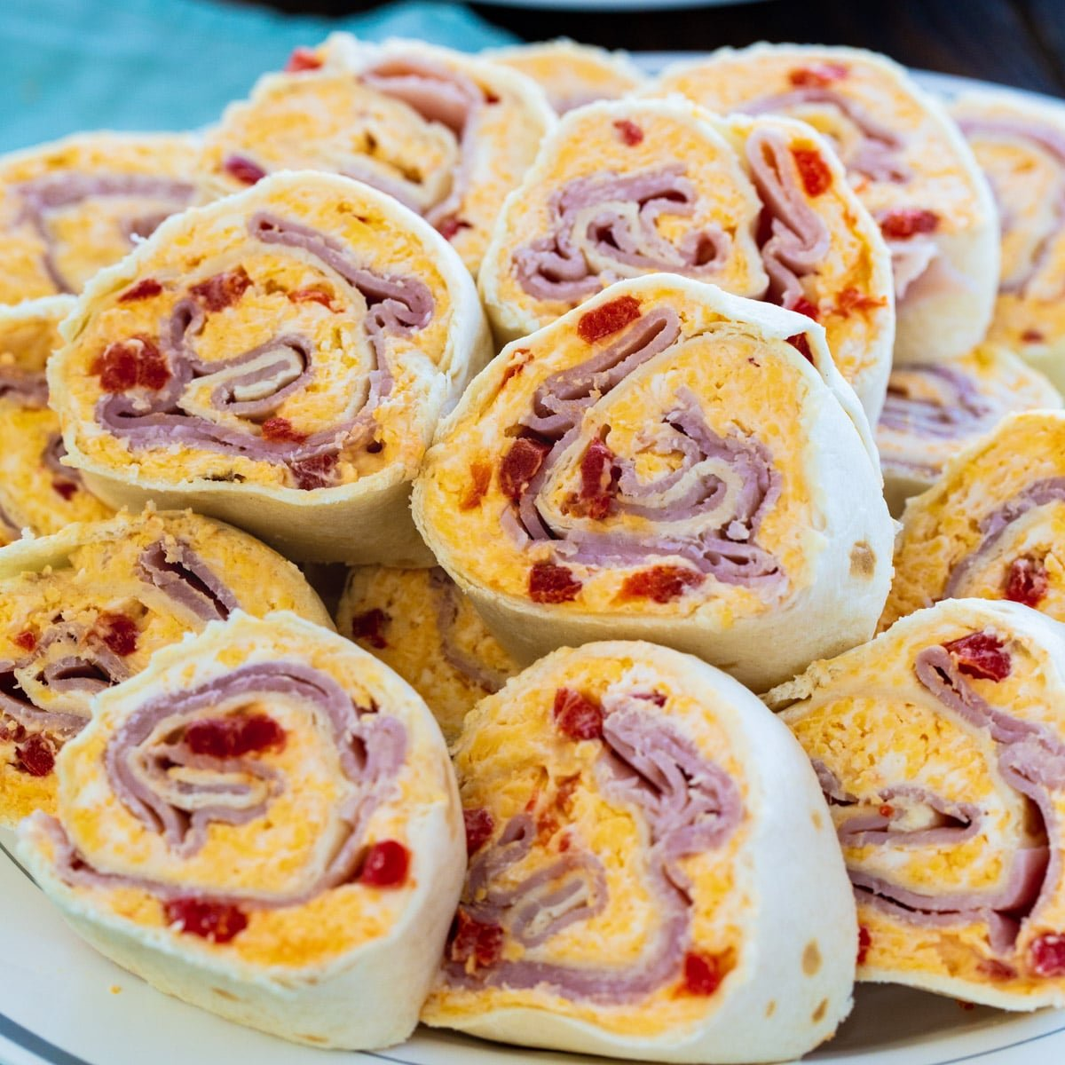Ham and Pimento Cheese Pinwheels piled up on a plate.