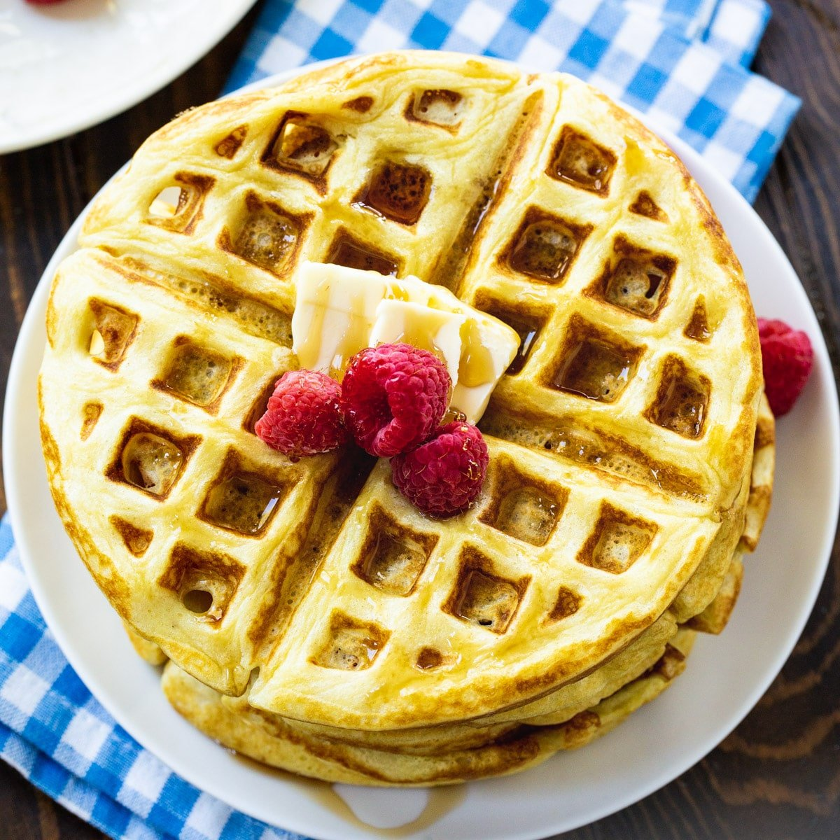 Overhead of stack of Overnight Yeast Waffles topped with butter and raspberries.