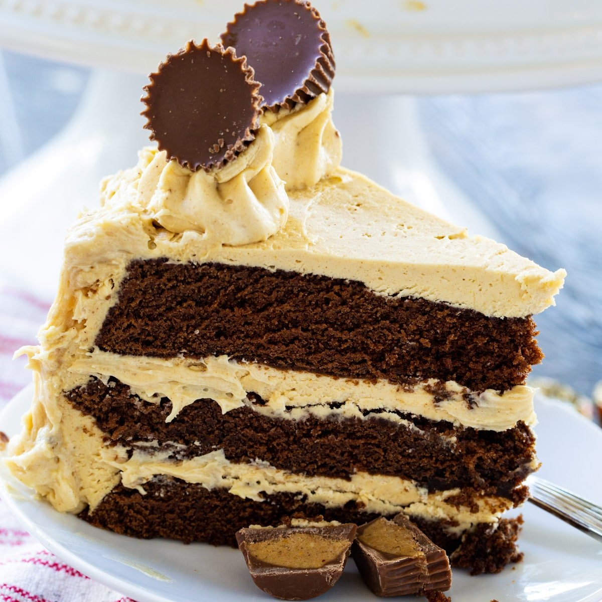 Slice of Peanut Butter Cup Cake topped with 2 mini peanut butter cups.