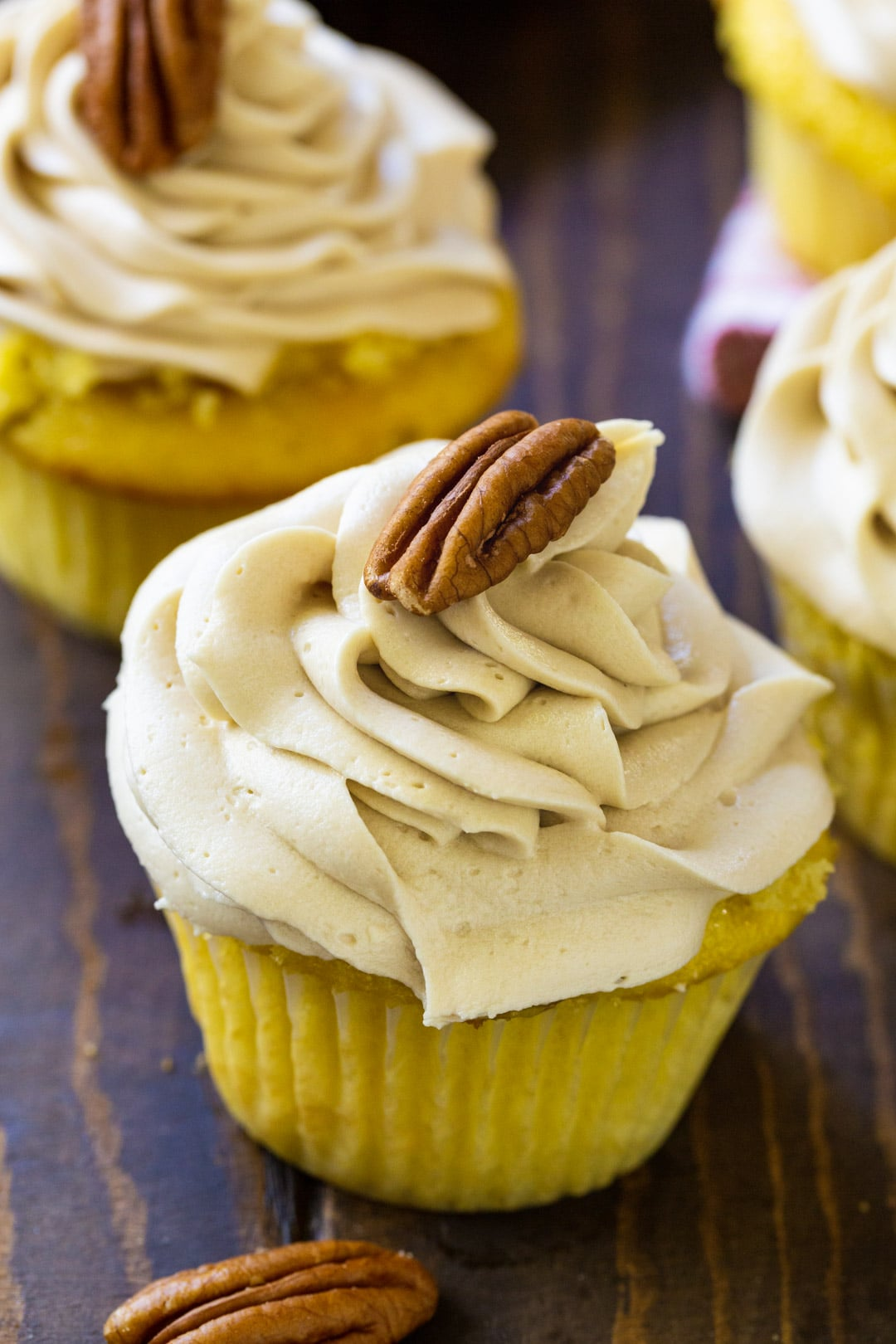 Pecan Pie Cupcakes topped with brown sugar frosting and a pecan.