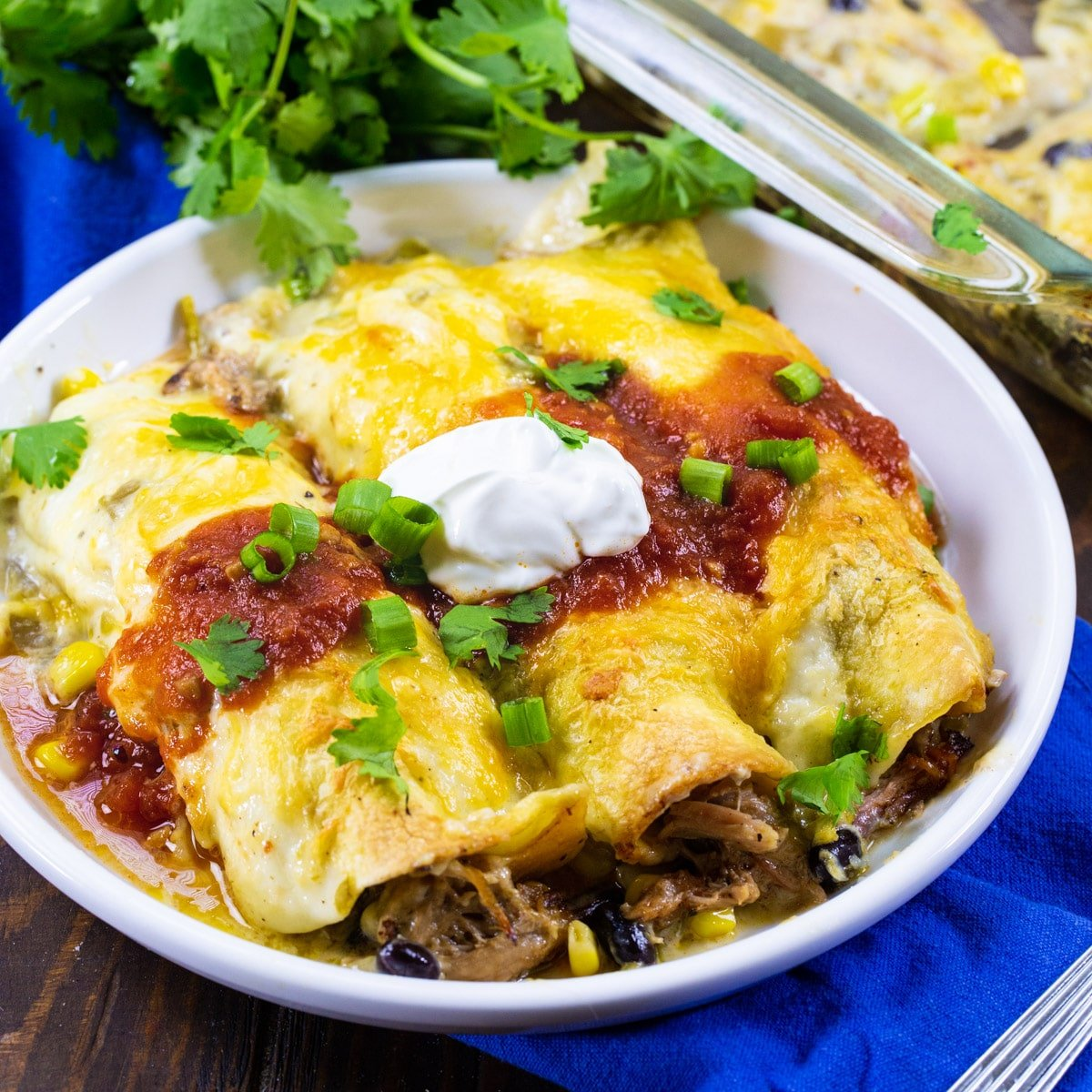 Three Pulled Pork Enchiladas topped with sour cream on a plate.