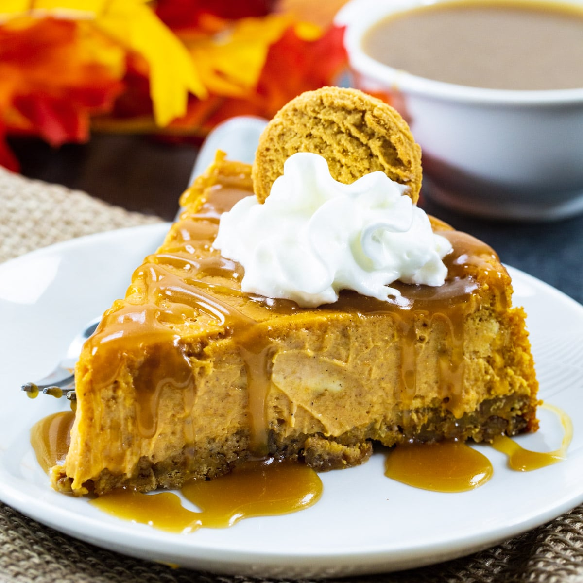 Slice of Pumpkin CHeesecake topped with whipped cream and drizzled with caramel sauce.