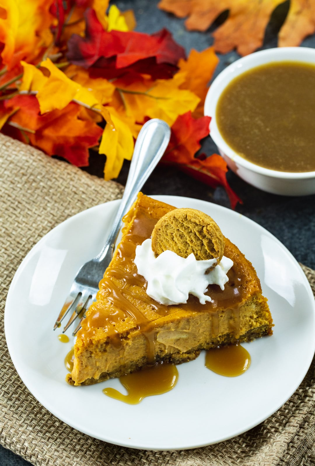 Pumpkin Cheesecake with Gingersnap Crust on a plate, plus fall leaves and a bowl of caramel sauce.