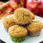 Muffins on a white plate with apples in background.