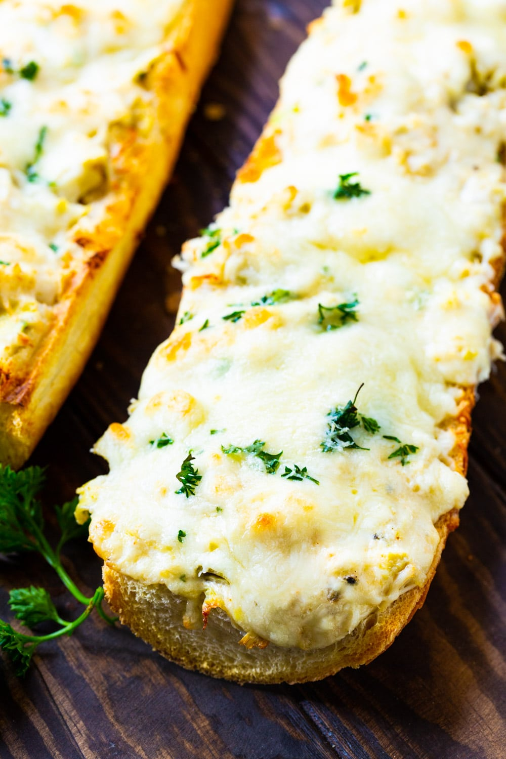 Long loaf of French bread topped with artichoke crab mixture.