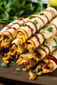 Pile of BBQ Chicken Taquitos on wooden board.