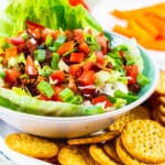 BLT Dip in a bowl surrounded by crackers.