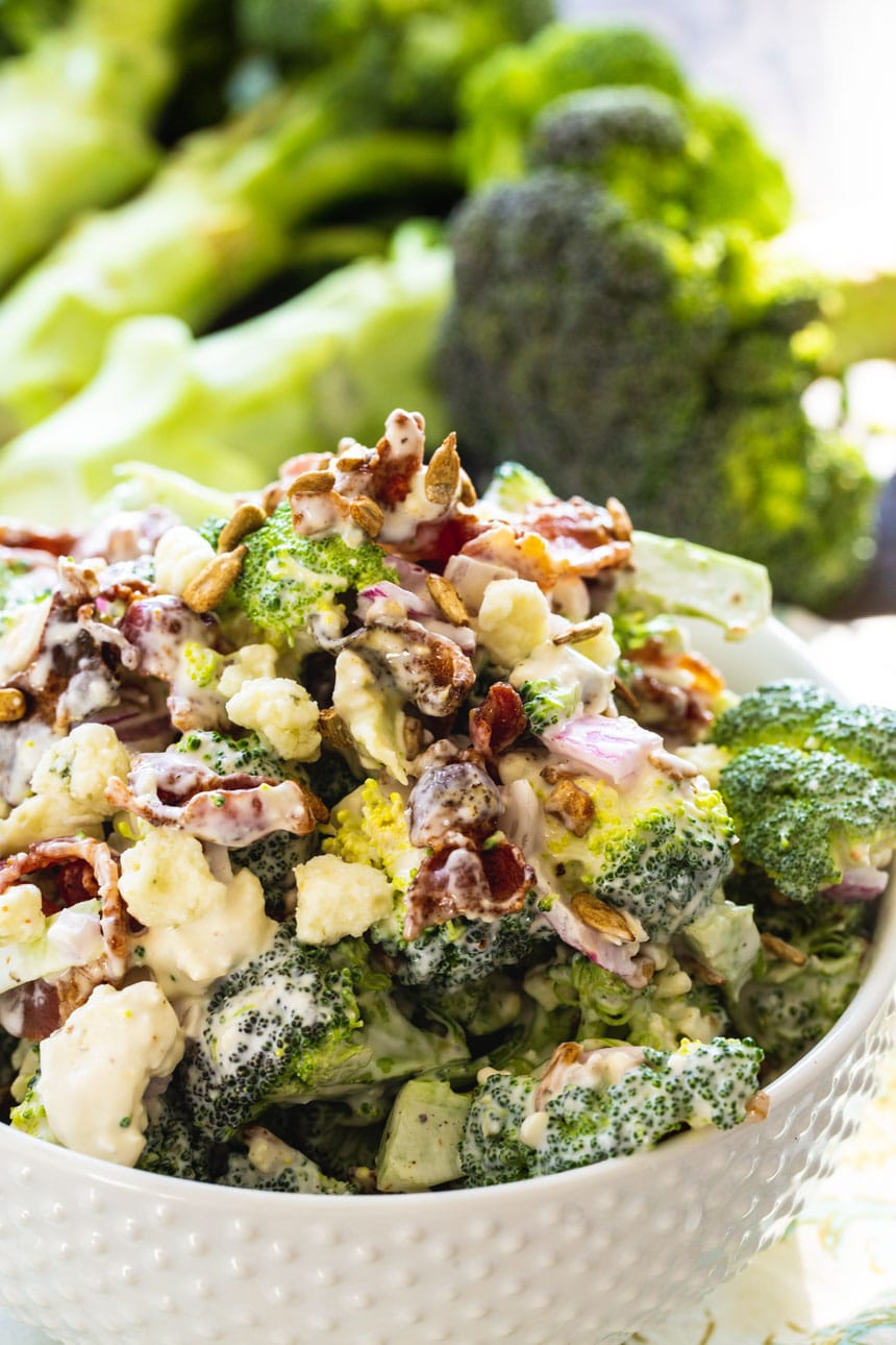 Bacon Broccoli Salad with a bunch of fresh broccoli in background.
