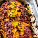 Meatloaf topped with bacon and cheddar cheese in baking pan.