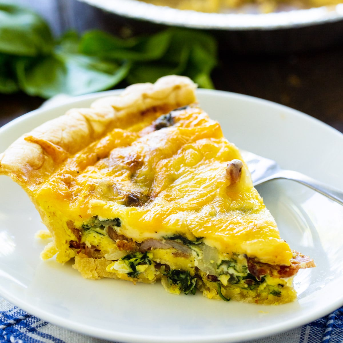 Slice of Bacon Florentine Quiche on a plate.