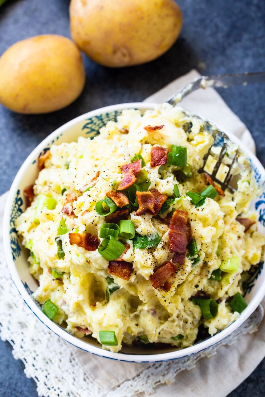 Overhead of Bacon-Green Onion Mashed Potatoes in a bowl with potatoes beside the bowl.