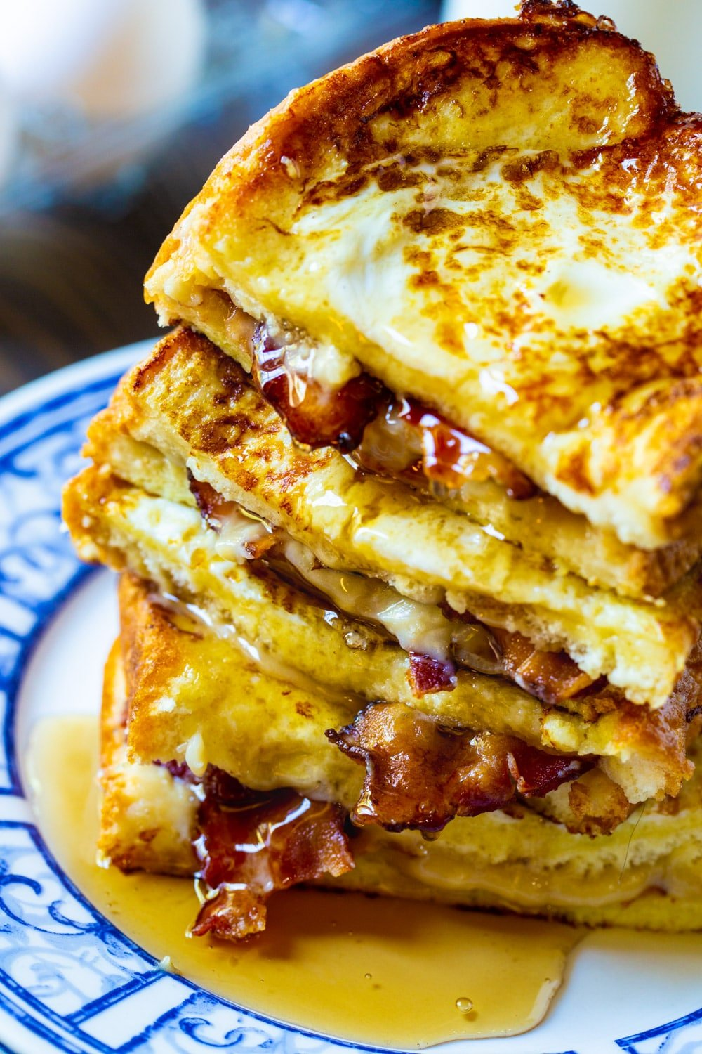 French Toast Stuffed with Bacon piled up with syrup dripping down.