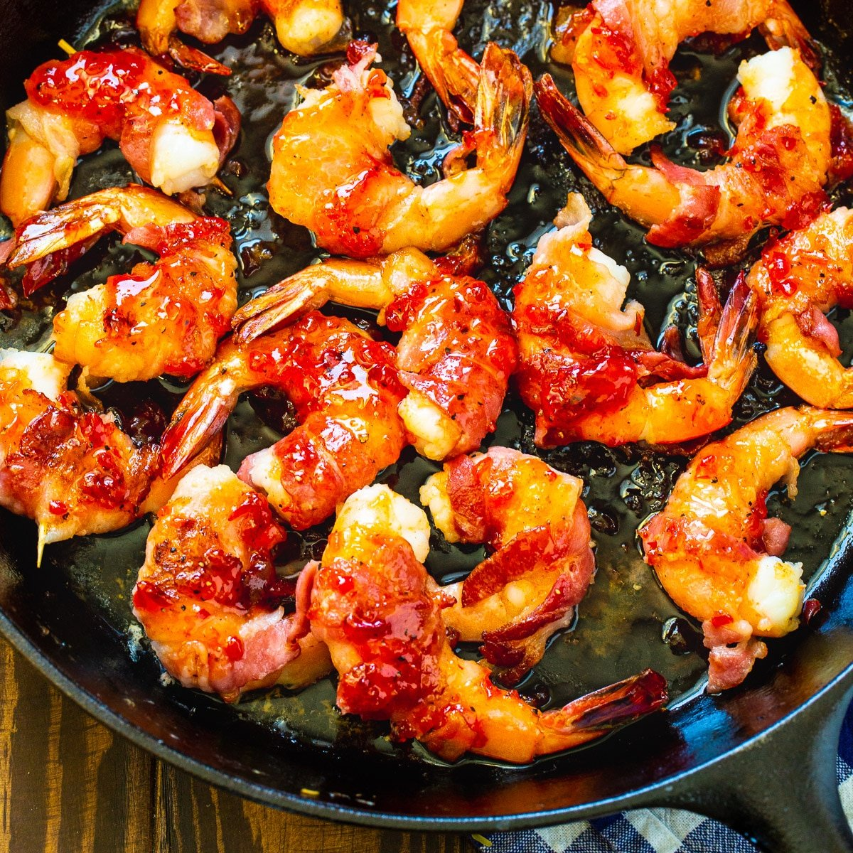 Bacon-Wrapped Shrimp with Pepper Jelly Glaze in a cast iron pan.
