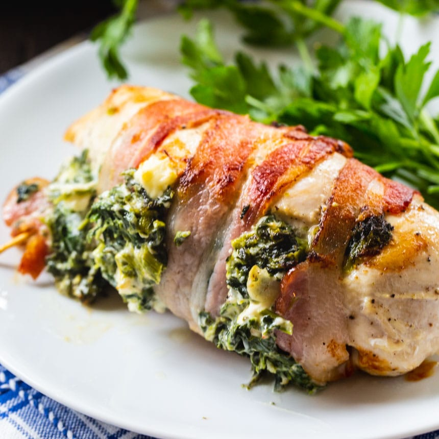 Stuffed Chicken Wrapped In Bacon on a white plate with parsley