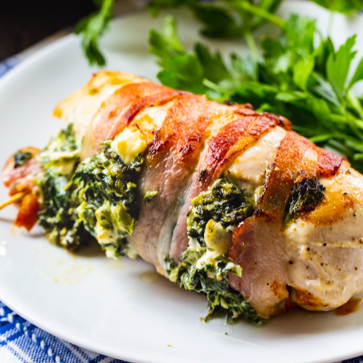 Bacon Wrapped Spinach and Feta Stuffed Chicken Breast on a plate with salad.