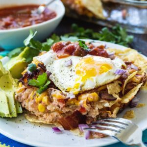 Chilaquiles with Bacon on a whte plate