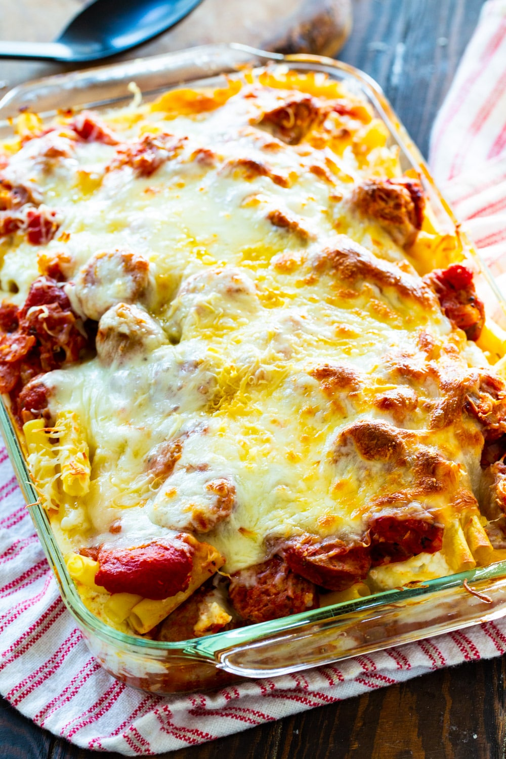 Baked ziti covered with melted cheese in baking dish.