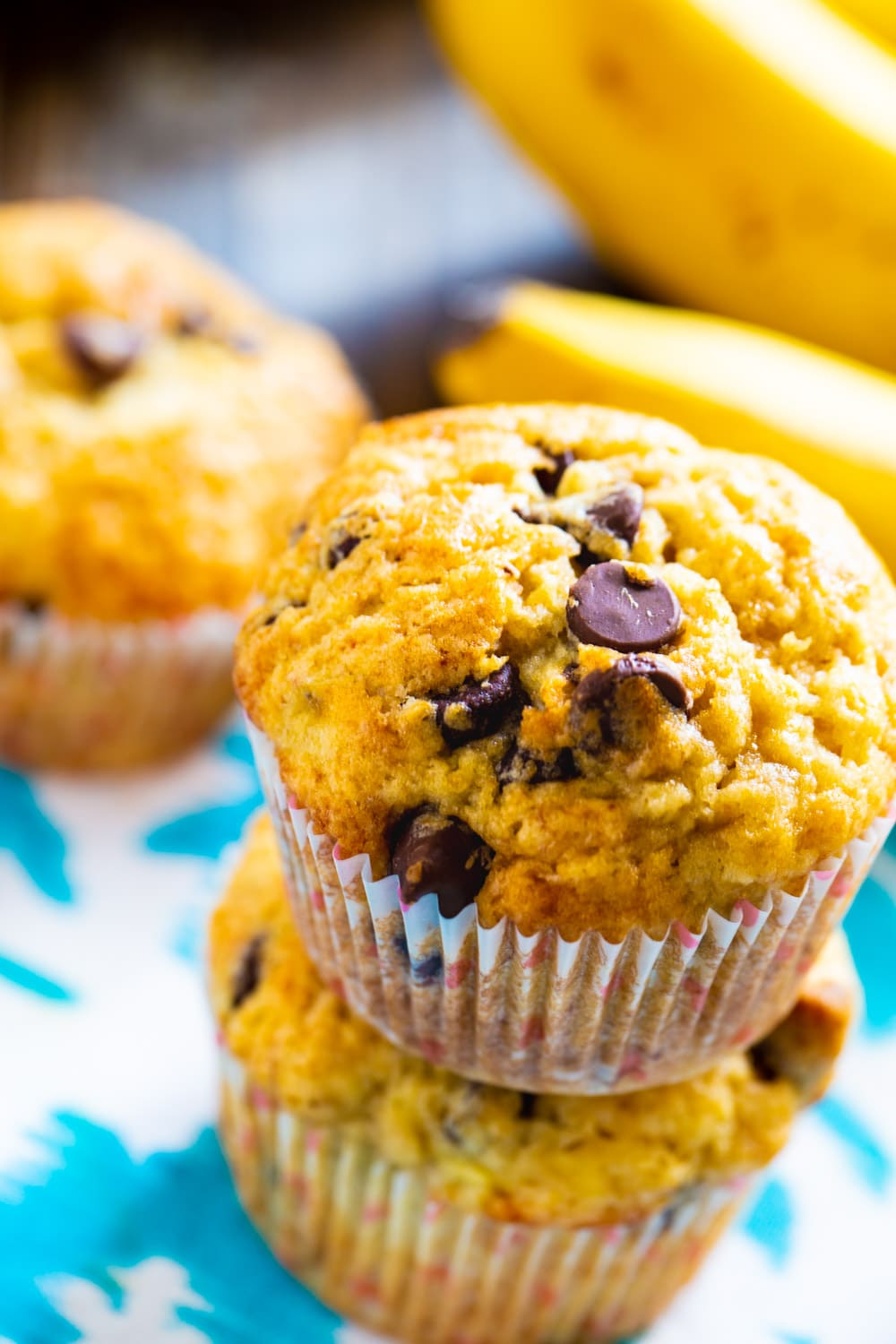 Two muffins stacked on top of each other with fresh bananas in background.