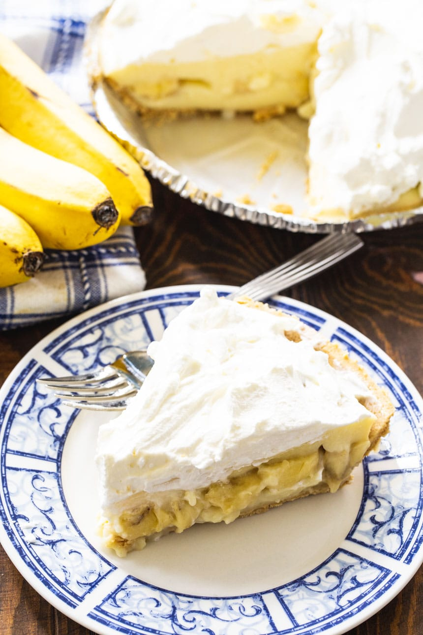 Slice of Banana Pudding Pie with bananas in background