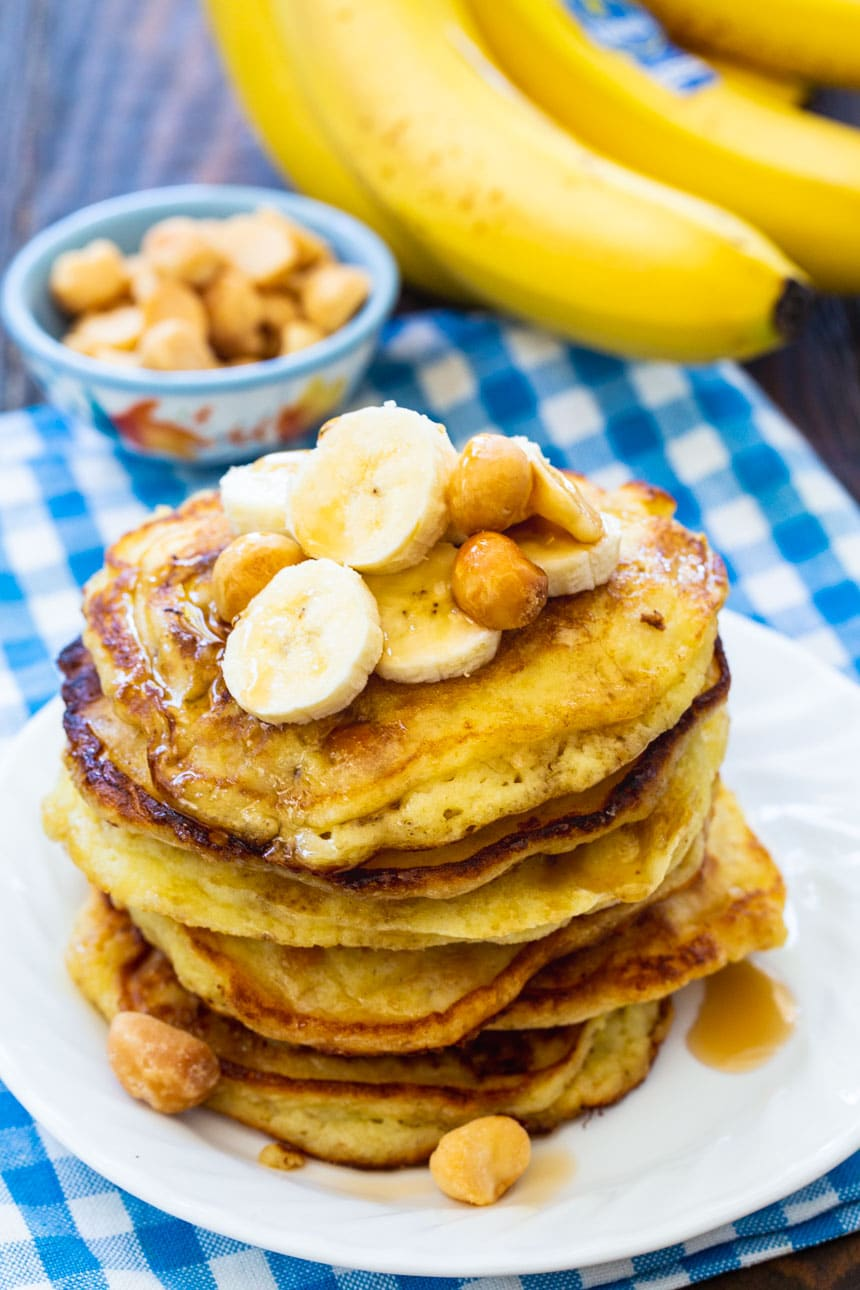 Banana Macadamia Nut Pancakes on a plate with bananas in background.