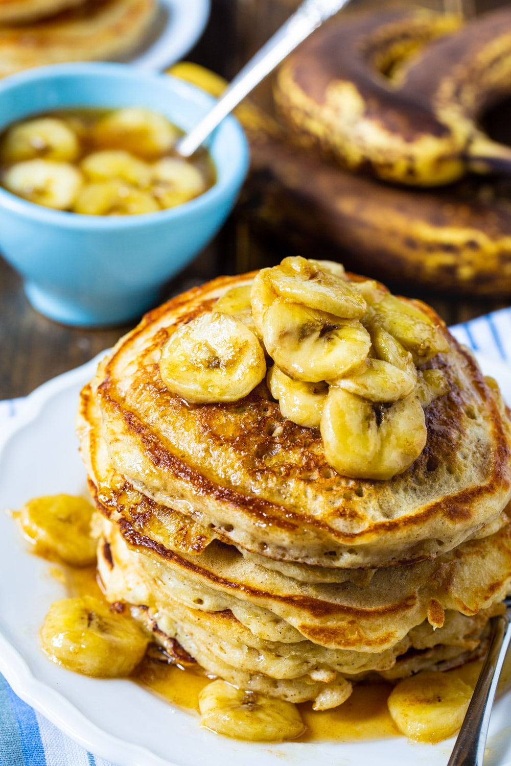 Pancakes stacked on a plate and topped with banana slices.
