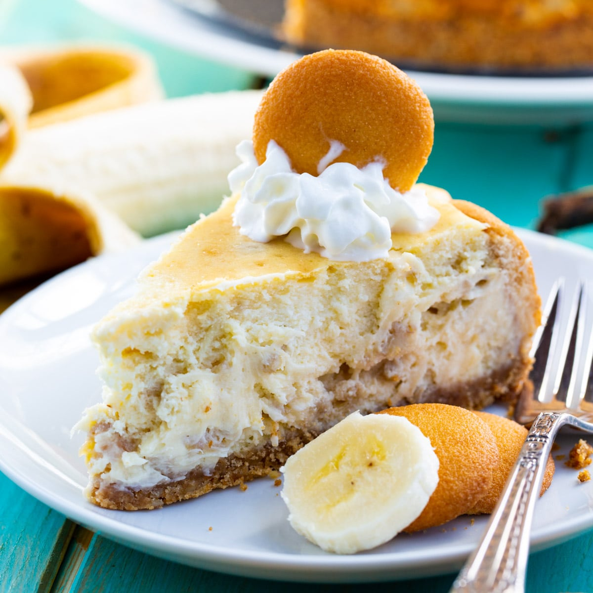 Slice of Banana Pudding Cheesecake topped with whipped cream and a vanilla wafer.