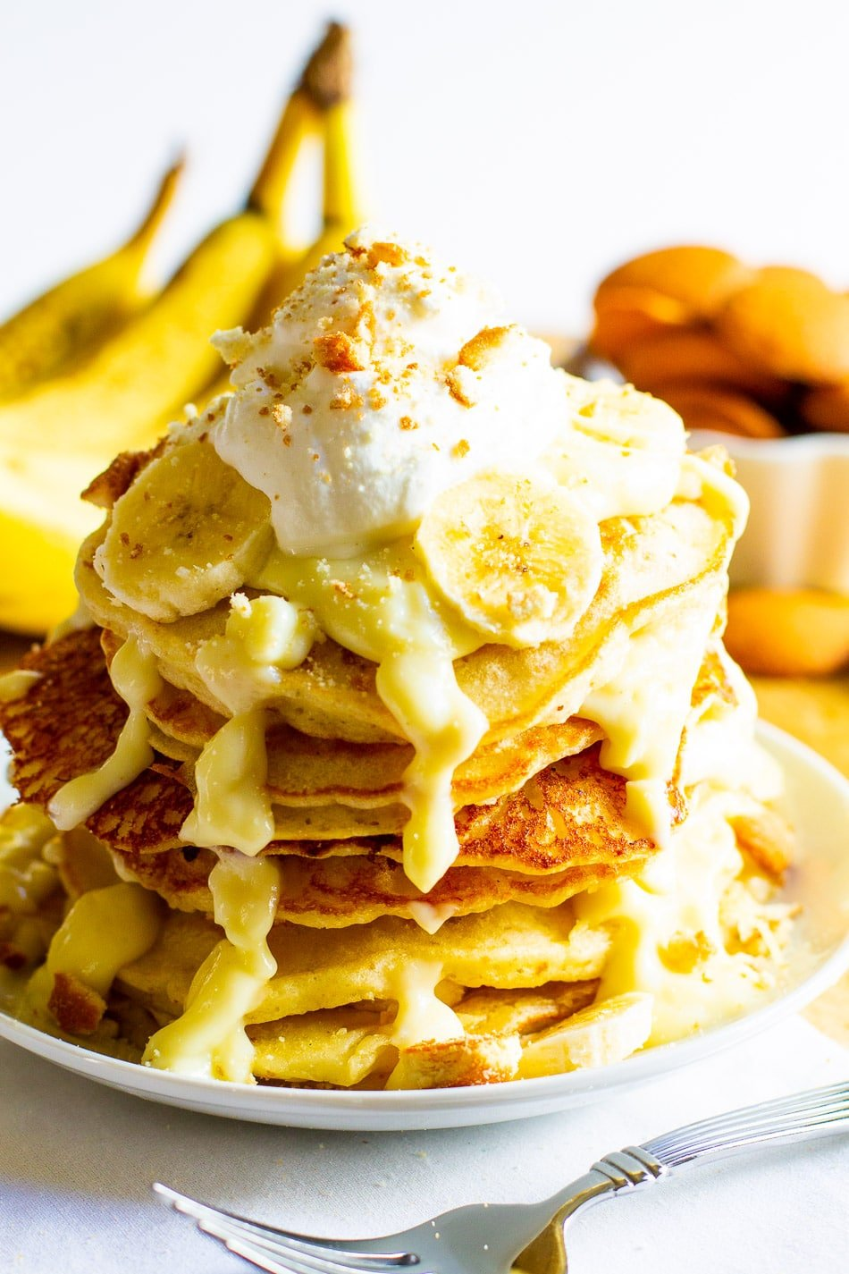 Stack of pancakes topped with whipped cream.