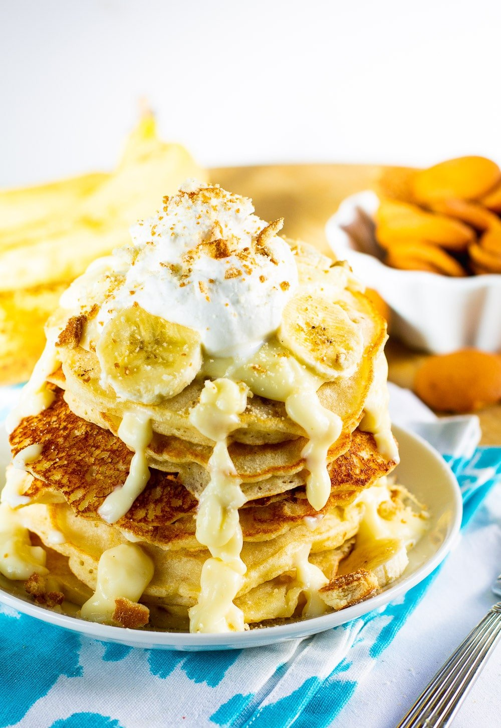 Pancakes on a plate with bananas and vanilla wafers in background.