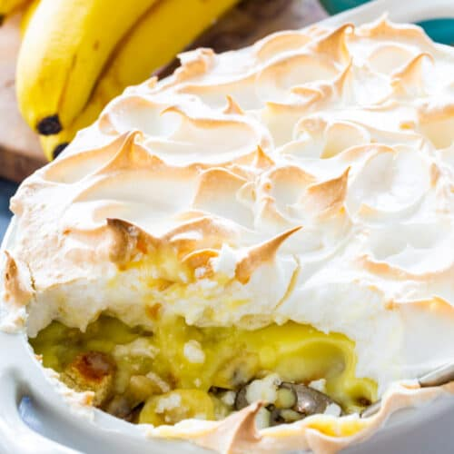 Banana Pudding with Meringue in baking dish with a serving scooped out.