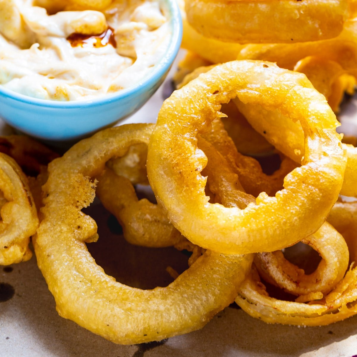 Beer Battered Onion Rings on a plate with dipping sauce.