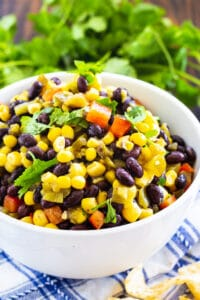 Black Bean and Corn Salsa in a bowl with bunch of cilantro behind it.