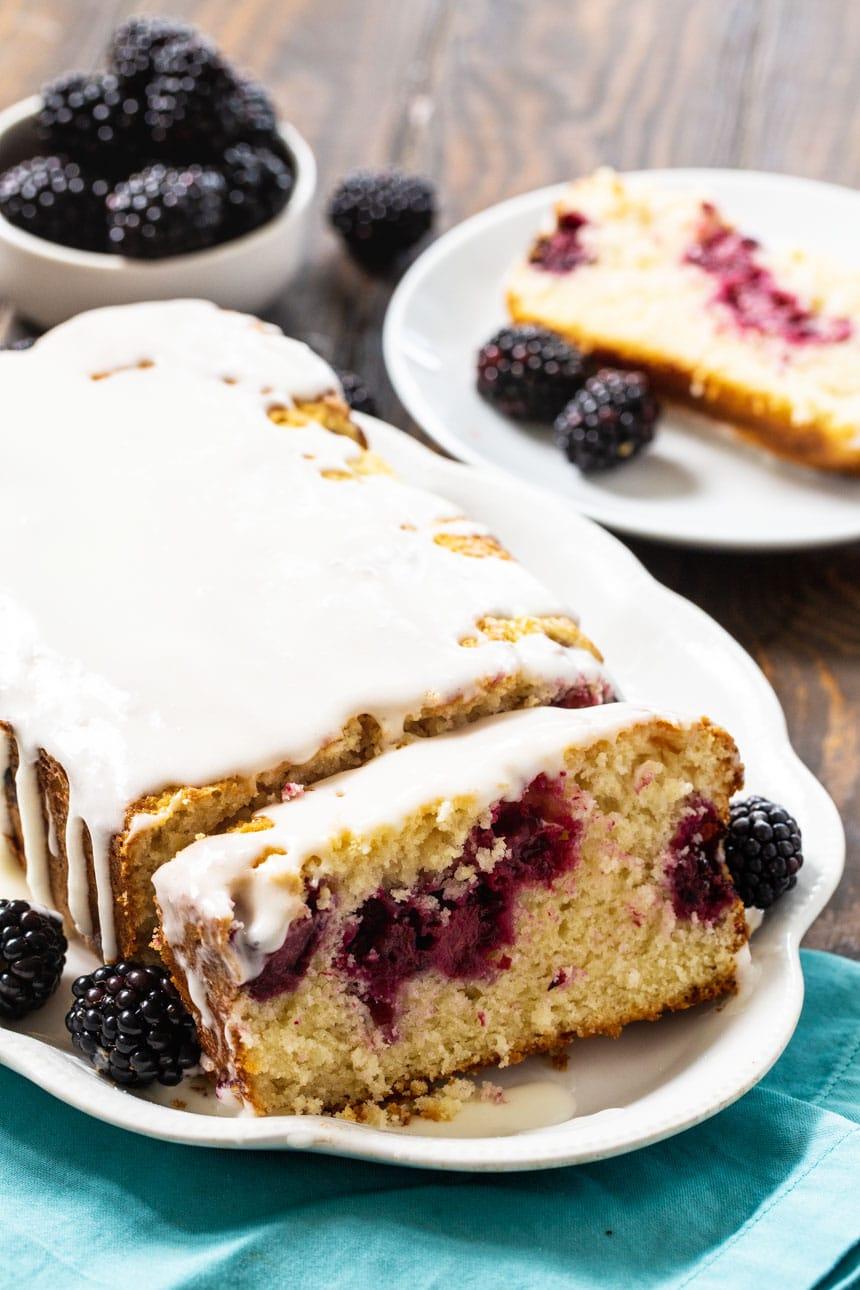 Blackberry Buttermilk Loaf Cake with fresh blackberries in background