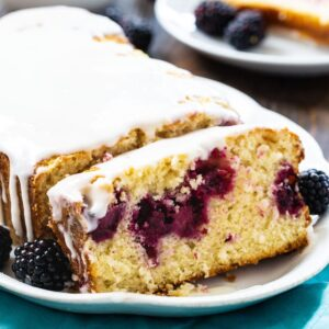 Buttermilk Loaf Cake with Blackberries on a white serving platter.