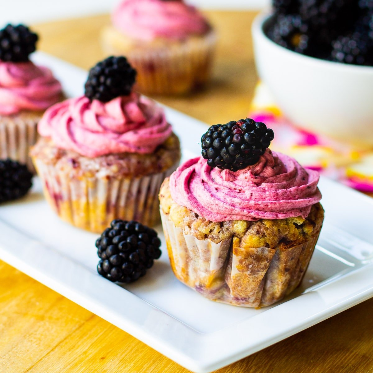 Cupcakes with Blackberries on a rectangular serving platter.