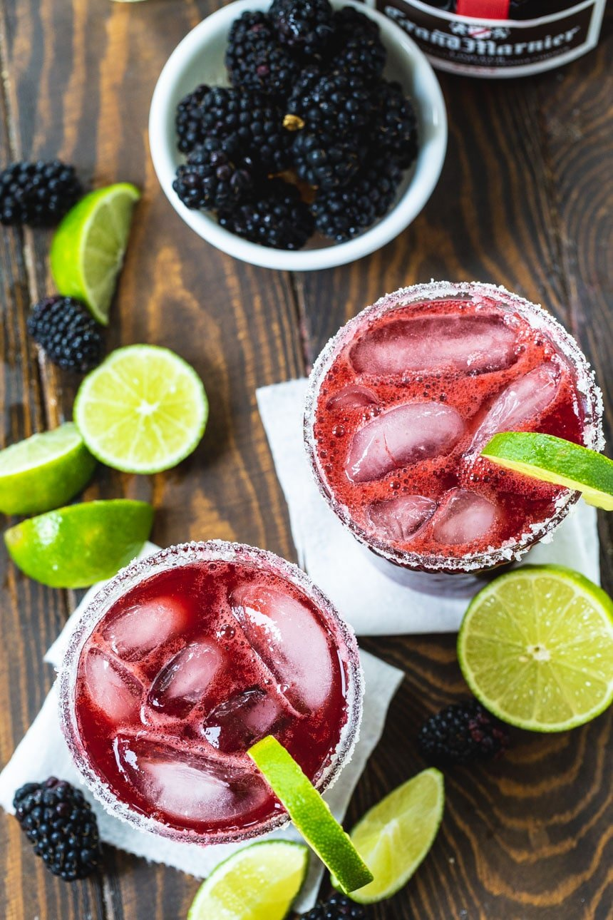 Overhead of Blackberry Margaritas with lime wedges and fresh blackberries scattered around them.