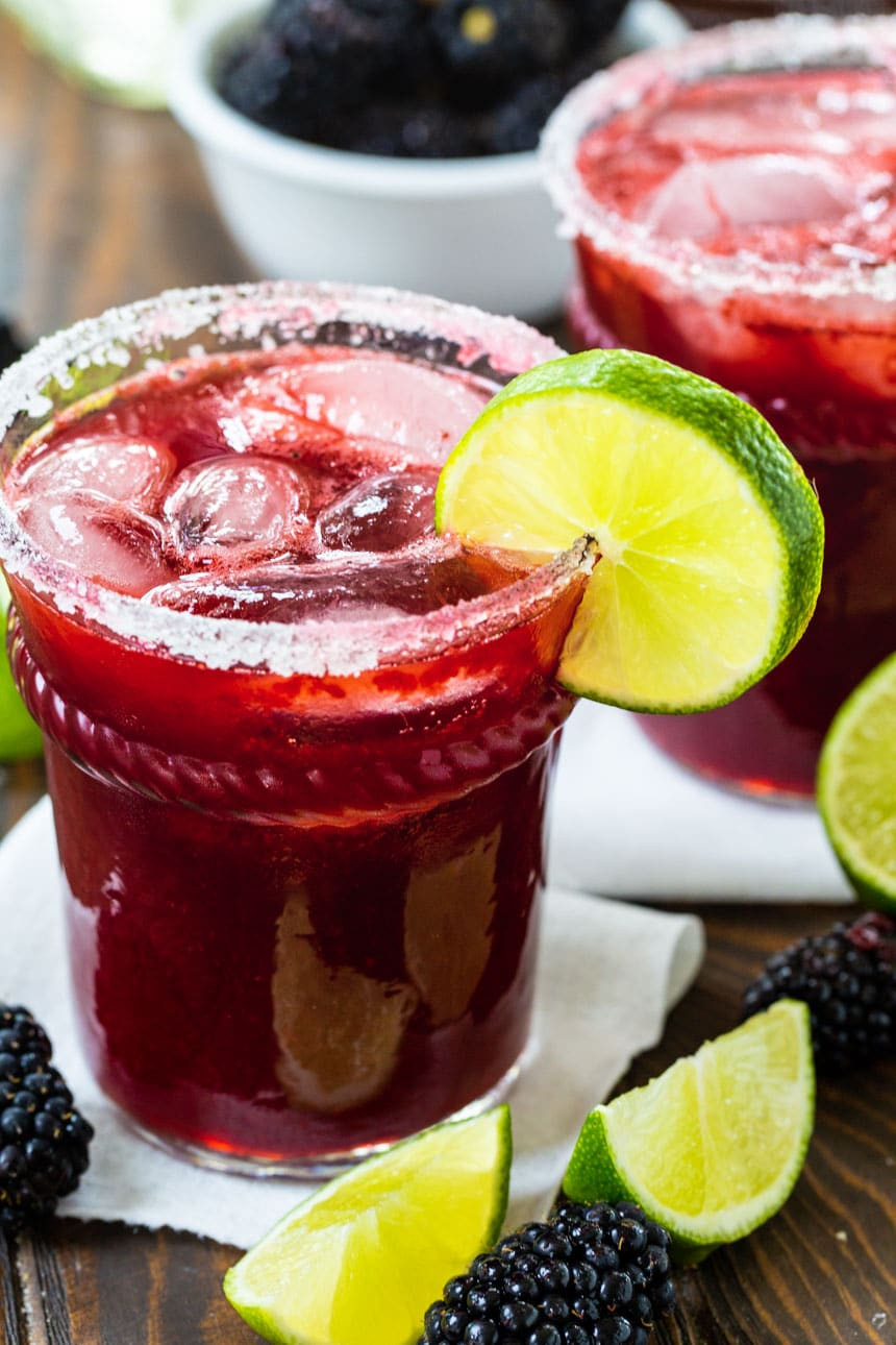 Margarita with blackberries in a glass with lime slice.