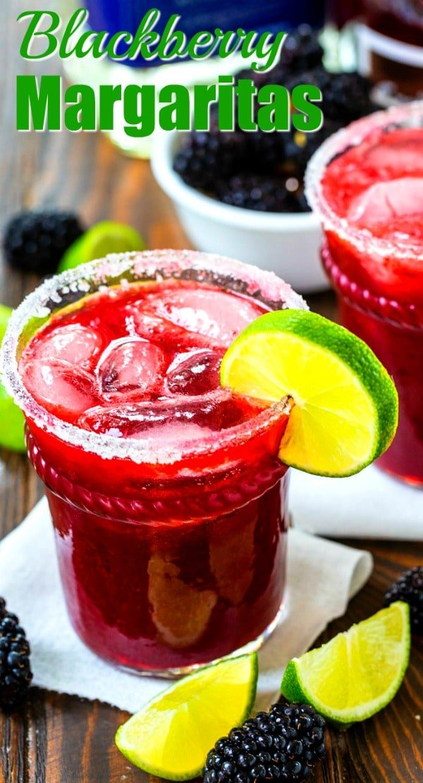 Blackberry Margaritas in a glass with lime wedges and fresh blackberries for decor.