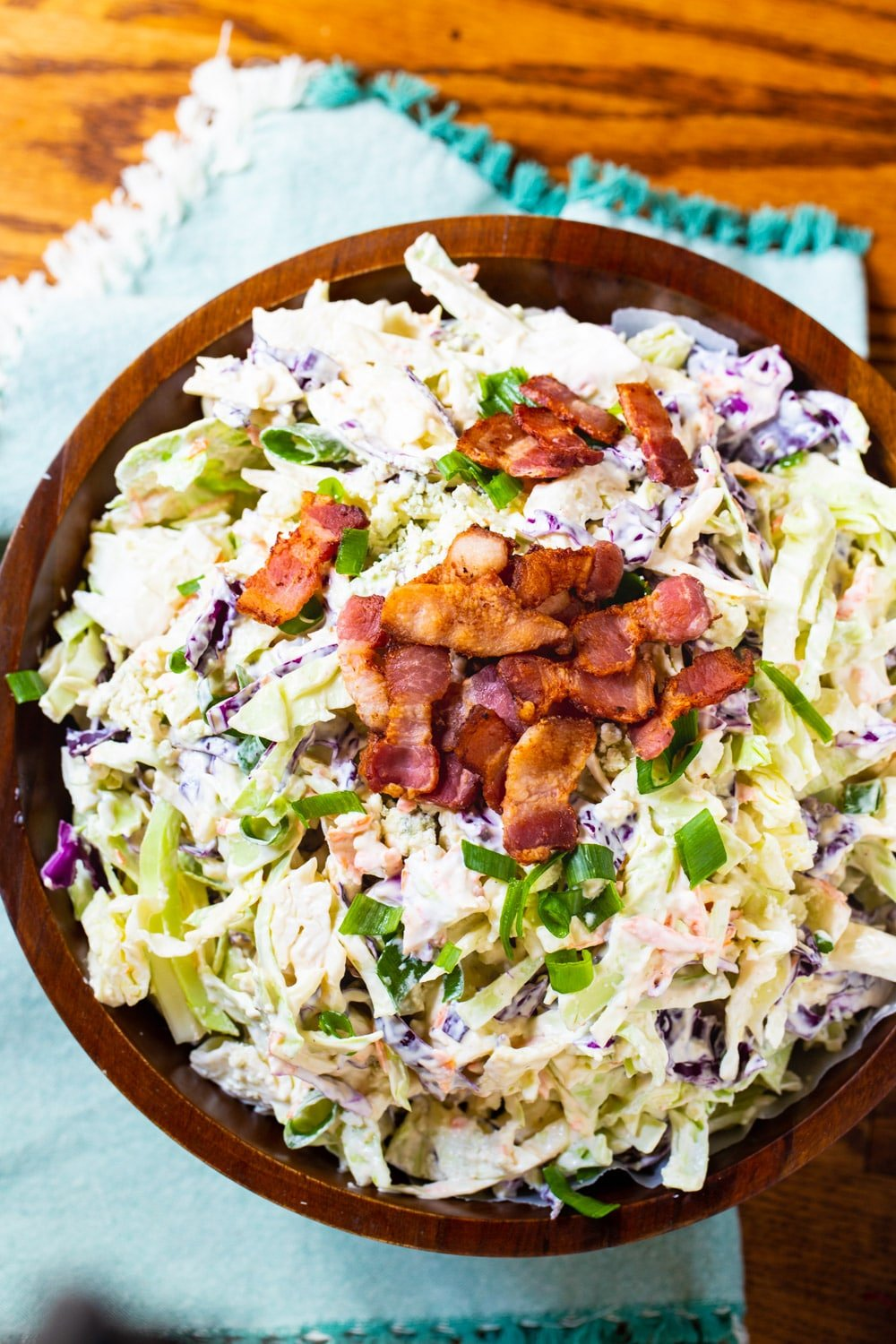 Coleslaw in wooden bowl with bacon crumbles on top.