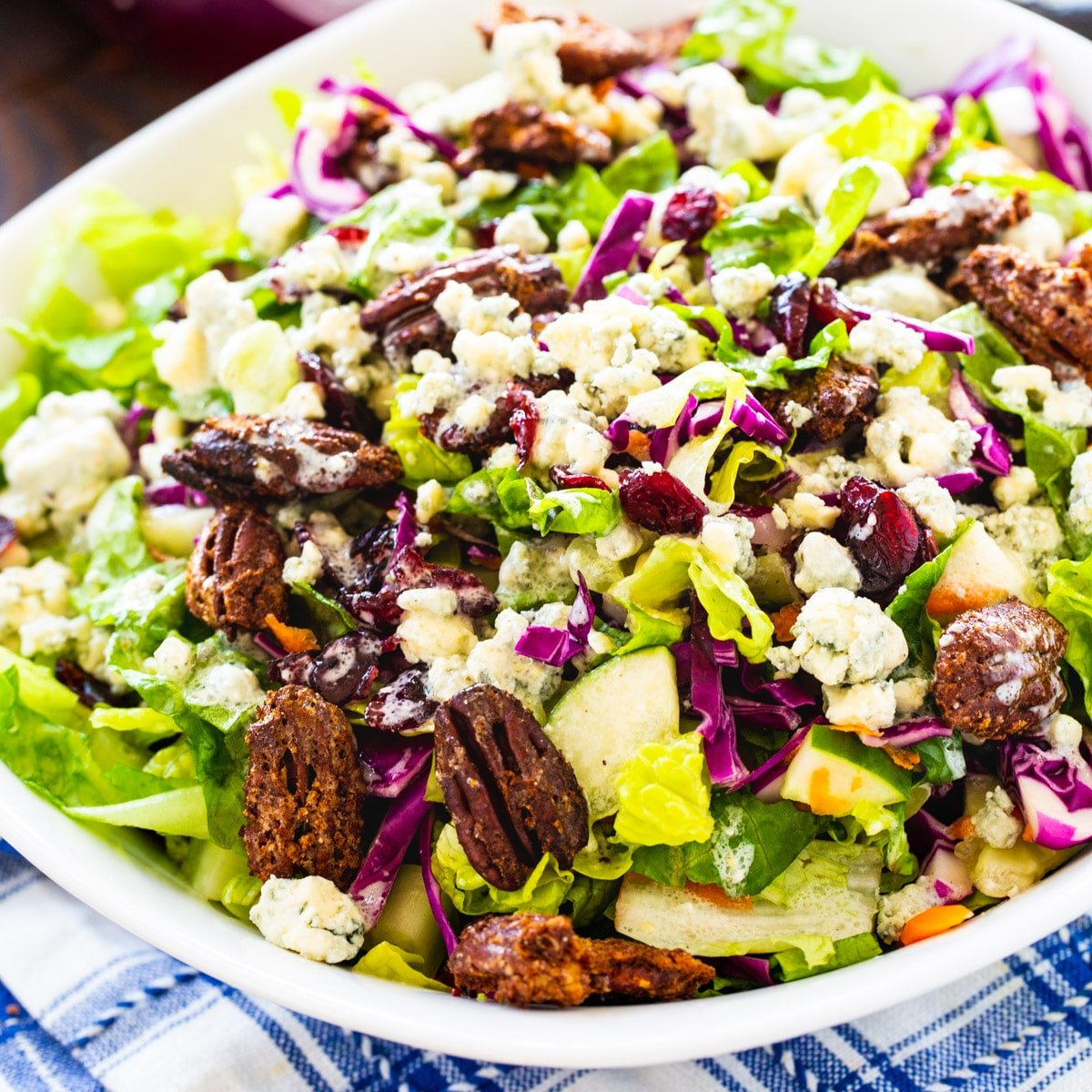 Blue CHeese Chopped Salad topped with Craisins and Pecans in a large white bowl.