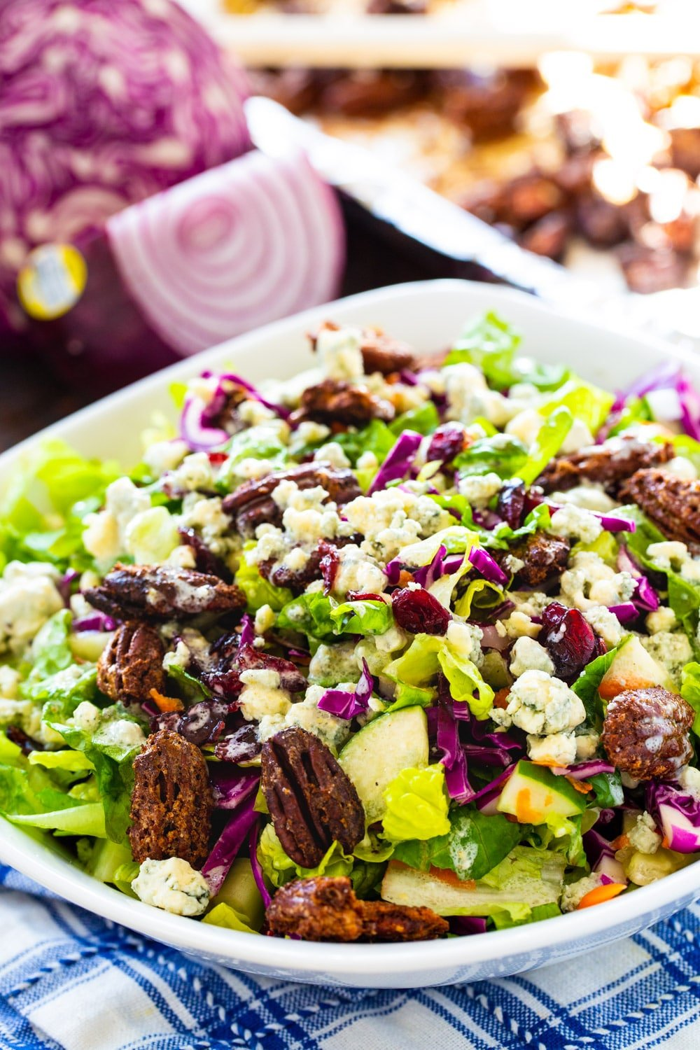 Chopped Salad in a large white bowl with cabbage in background.