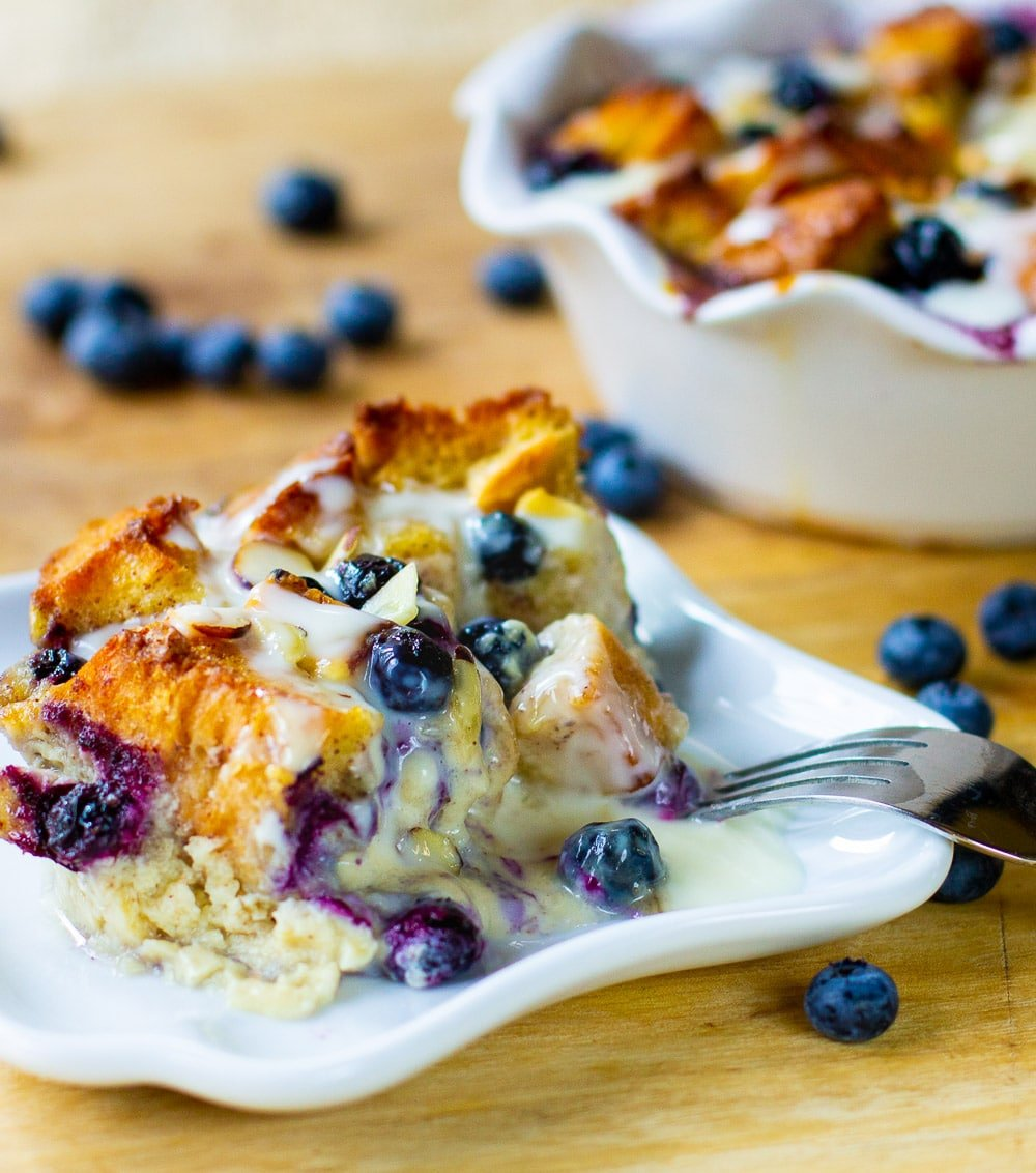 Slice of Bread Pudding with blueberries on a plate.