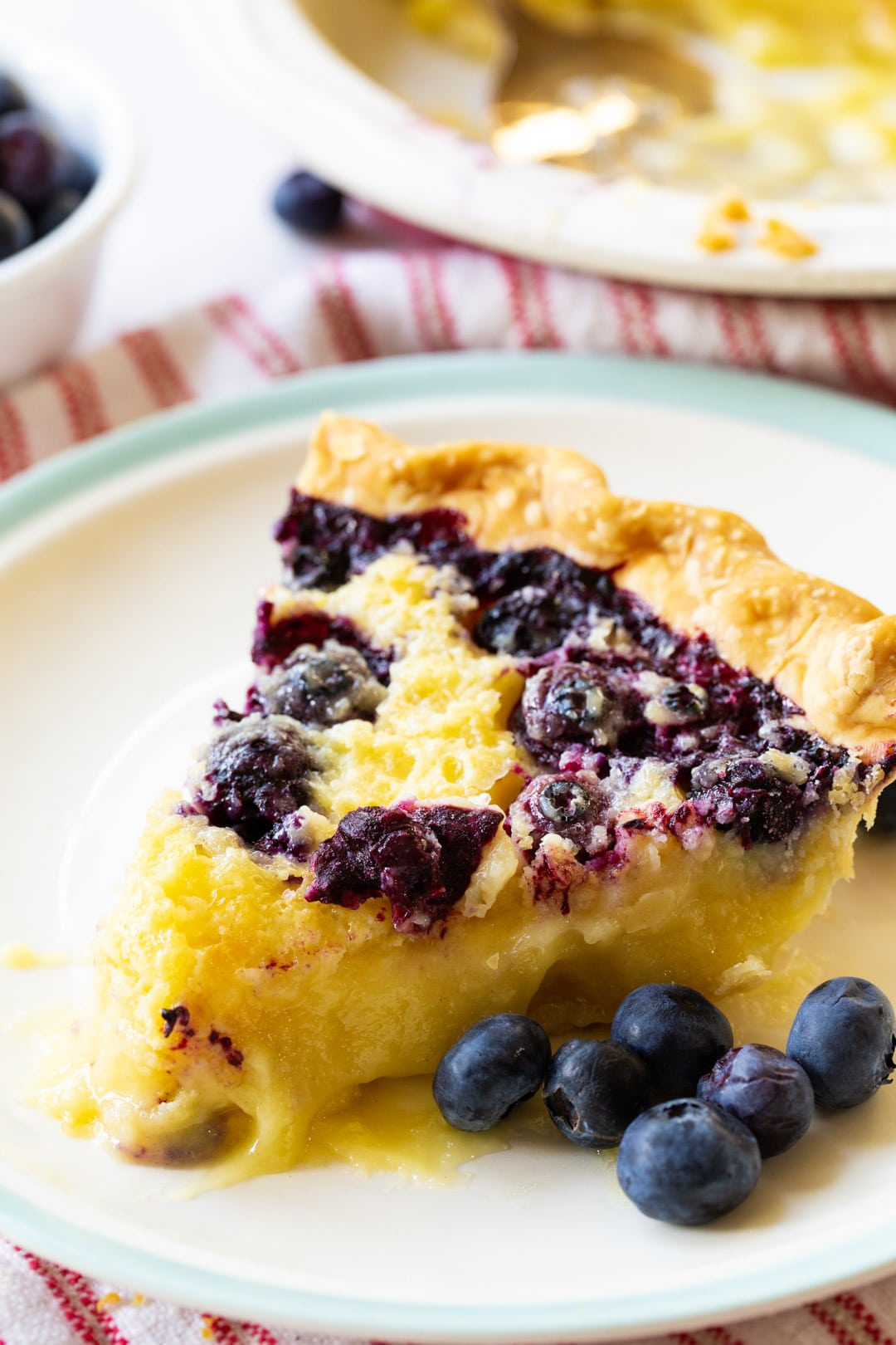 Slice of pie on a plate with blueberries.