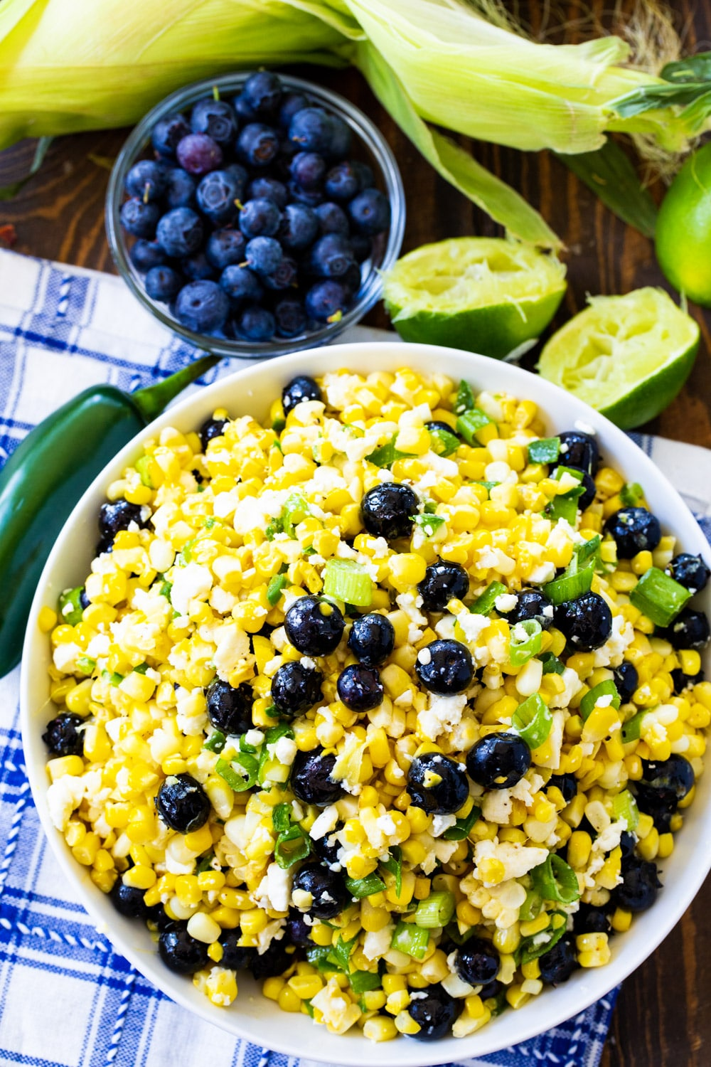Blueberry, Corn and Feta Salad in a bowl surrounded by fresh blueberries and lime halves.