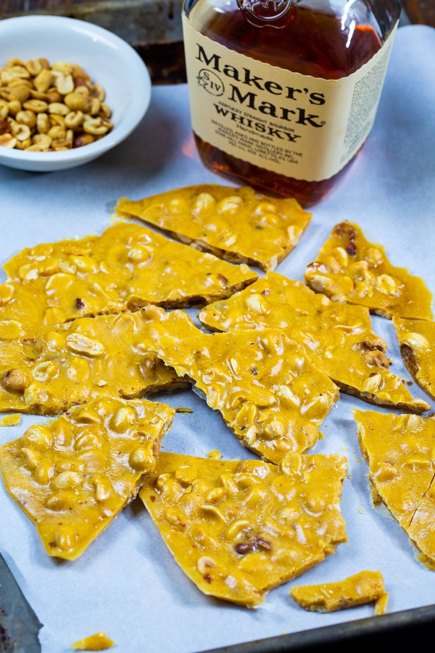 Peanut Brittle with bottle of bourbon and bowl of peanuts.