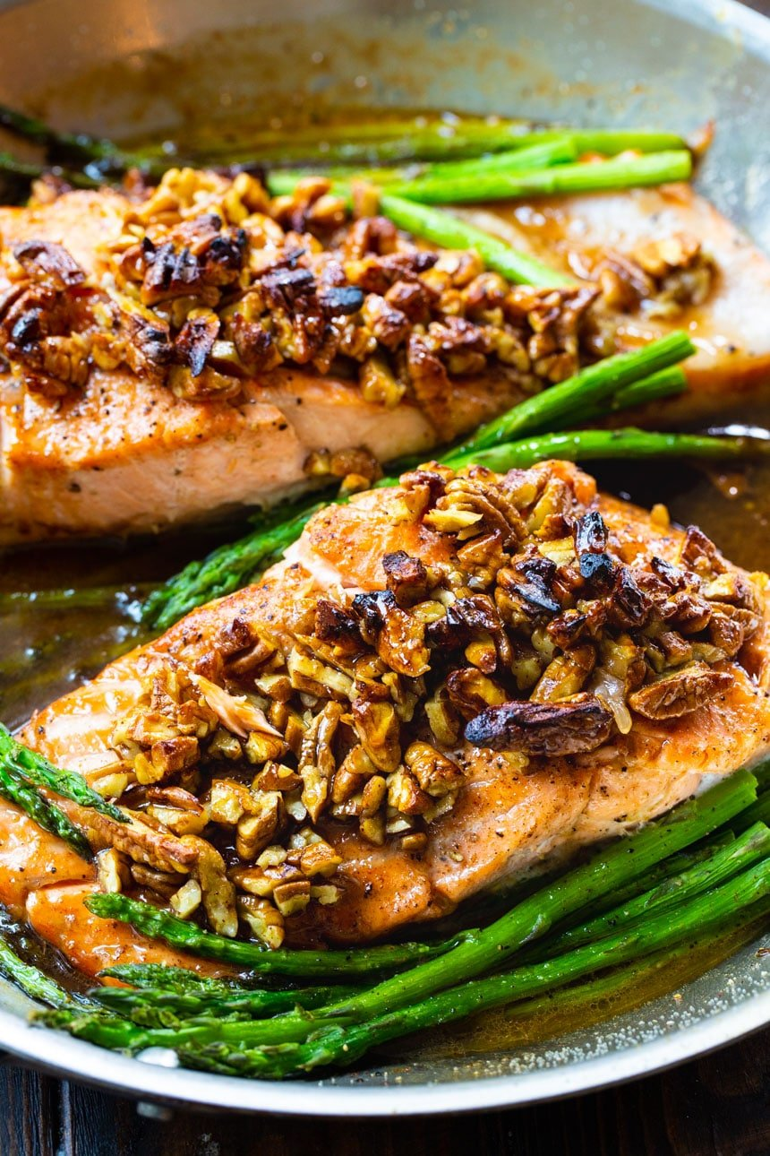 Bourbon Pecan Glazed Salmon fillets in a pan with asparagus