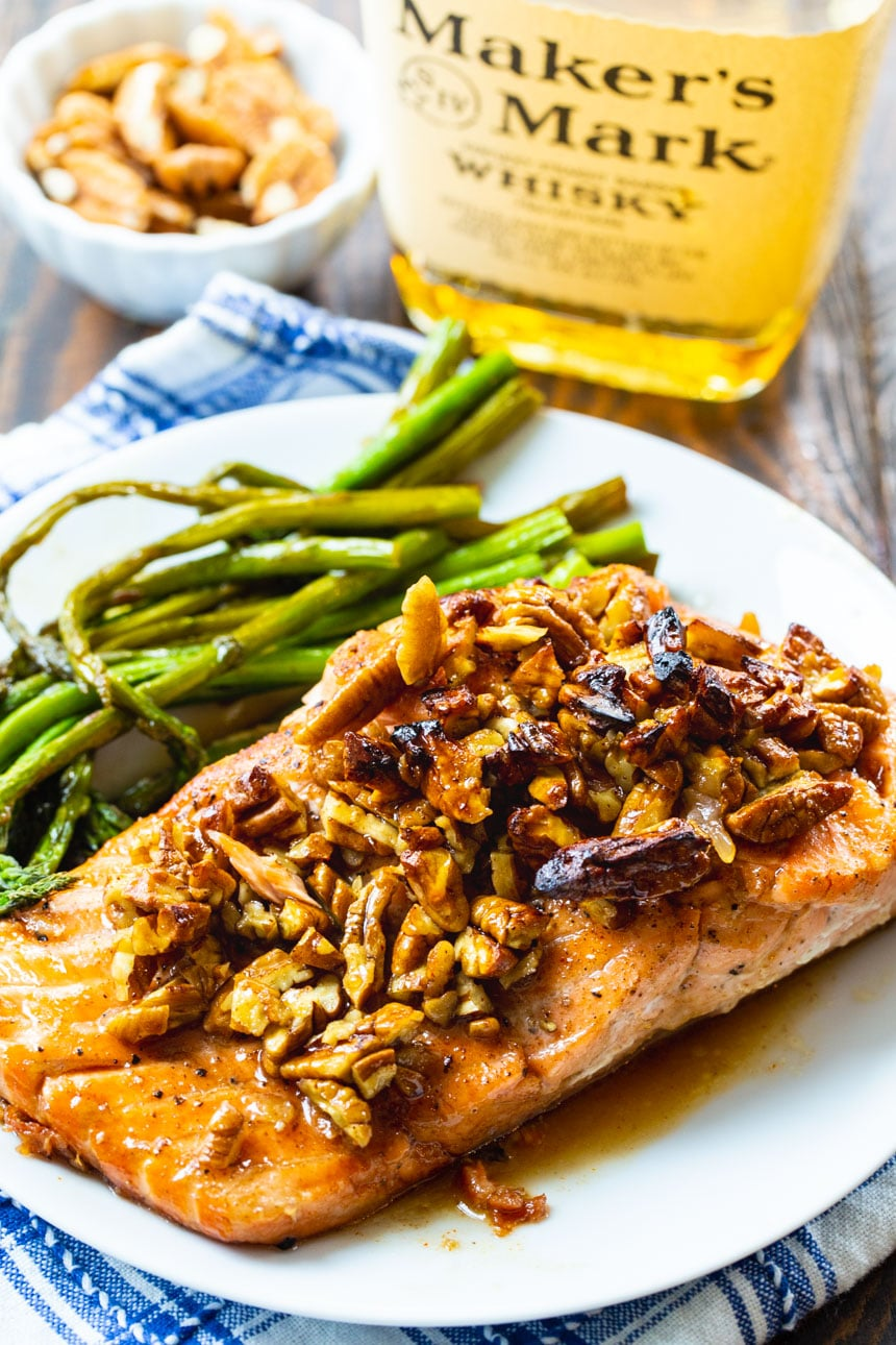 Salmon fillets with bourbon-pecan glaze on a white plate with asparagus