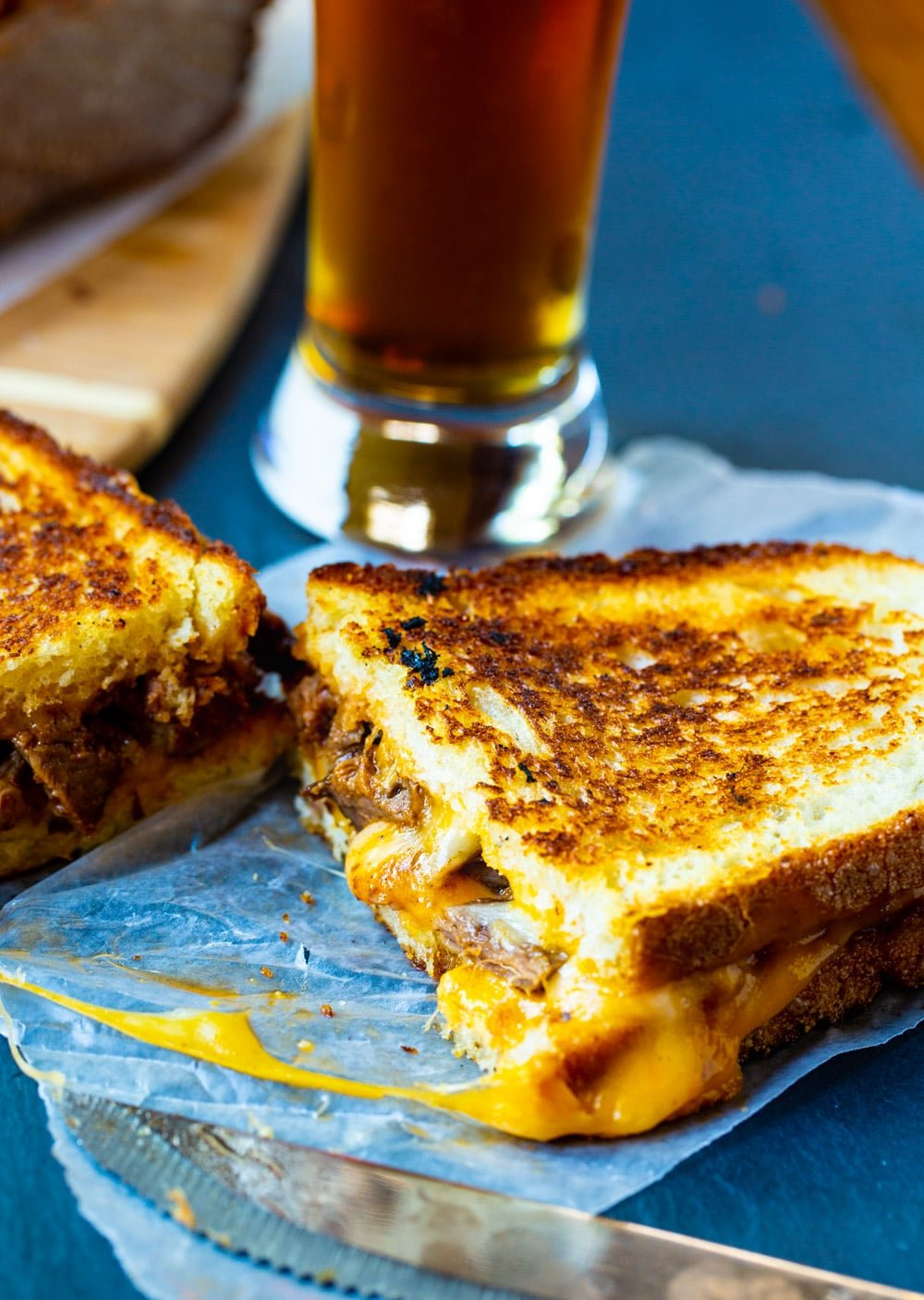 Grilled Cheese cut in half with a glass of beer.